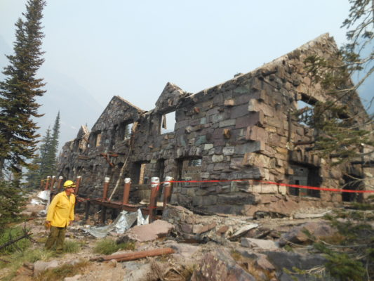 Glacier Park staff and engineers inspect the damaged Sperry Chalet dormitory building after it burned in the Sprague Fire on August 31