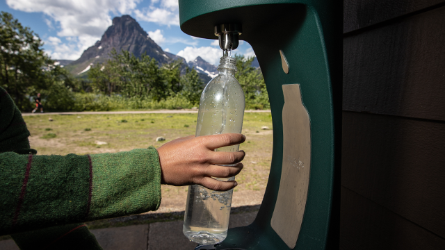 Water bottle under filling station with mountain in background.