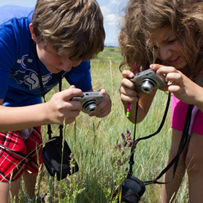 Two kids taking photos of plants