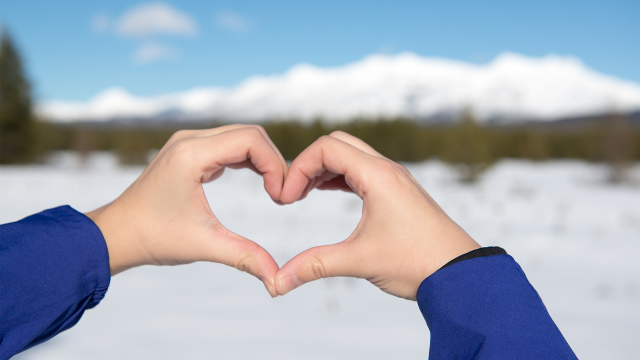 Hands form the shape of a heart in front of snowy mountain landscape