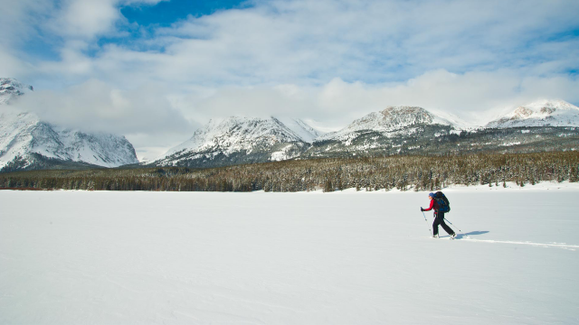 A cross country skier skis across a frozen lake in Glacier National Park