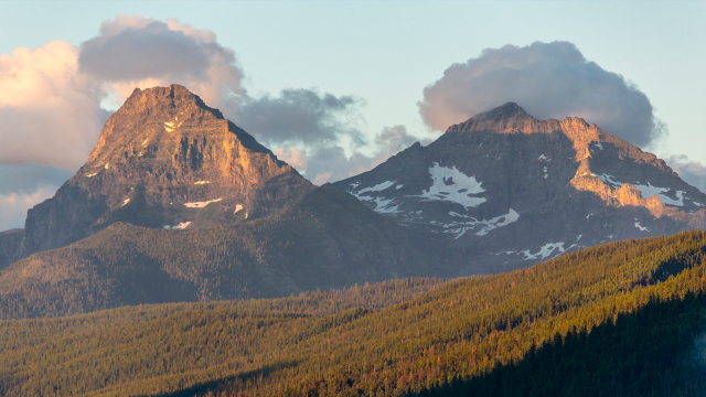 Two prominent mountain peaks glow orange during sunset in Glacier National Park