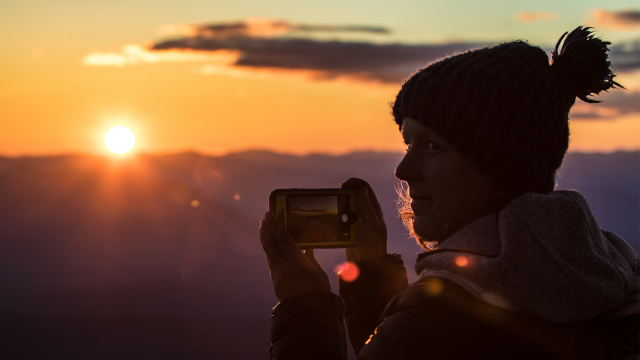 A woman takes a photo of a golden mountain sunset
