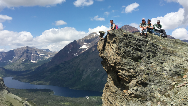 A group of hikers in the Piikani Lands Crew pose for a photo high above a mountain landscape with an alpine lake in the background