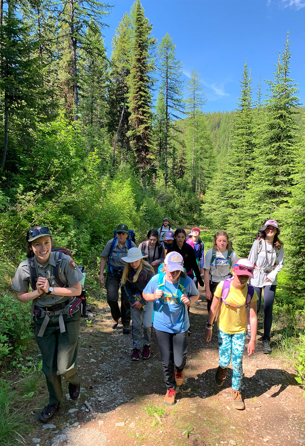 A group of girls hike on a trail with a park ranger in Glacier National Park