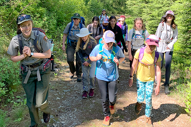 Ranger hiking on trail with a group of girls.