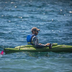 Kayaker paddling on lake.