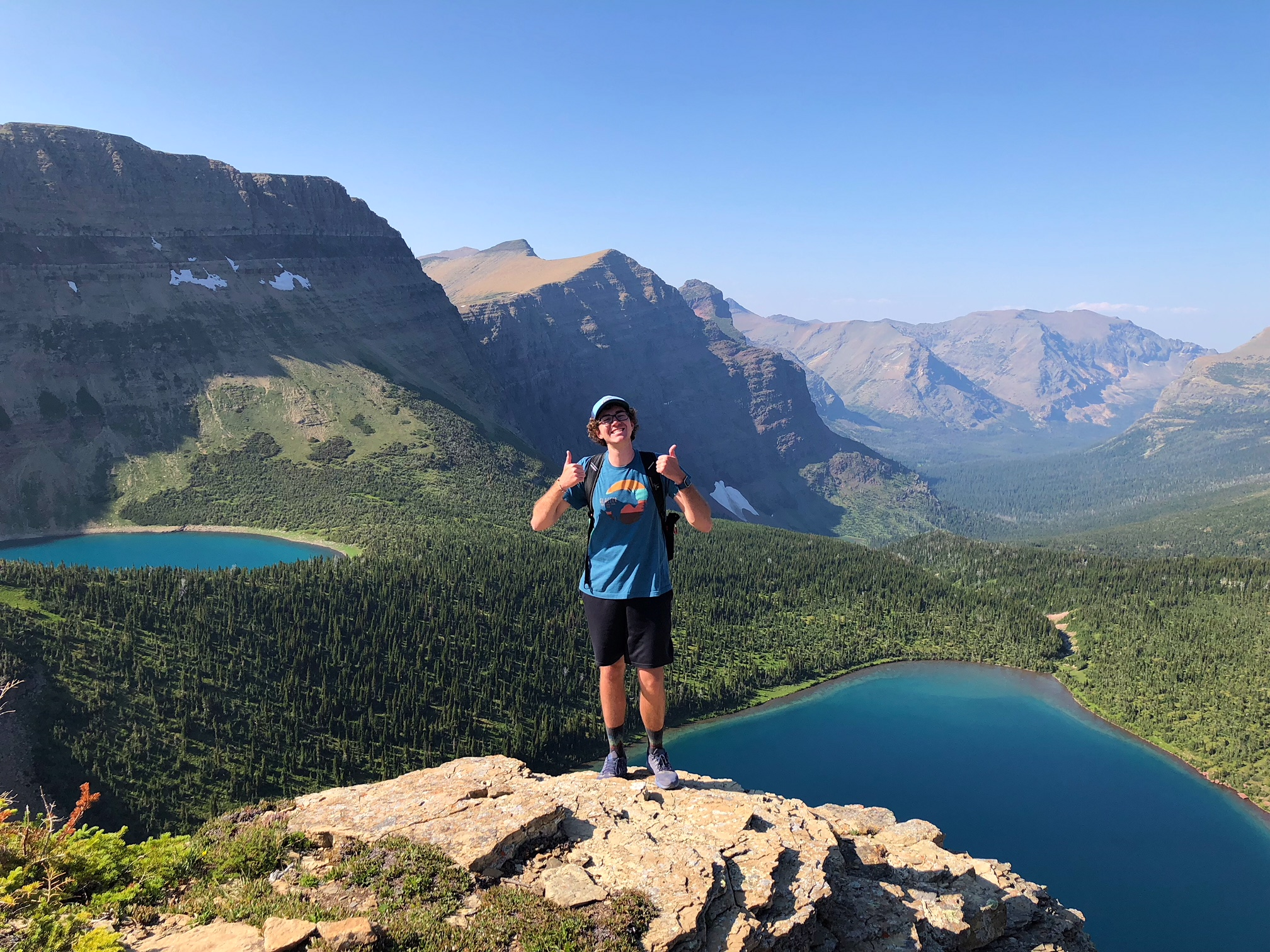 A man smiles and holds his thumbs up with mountains and turquoise lakes in the background