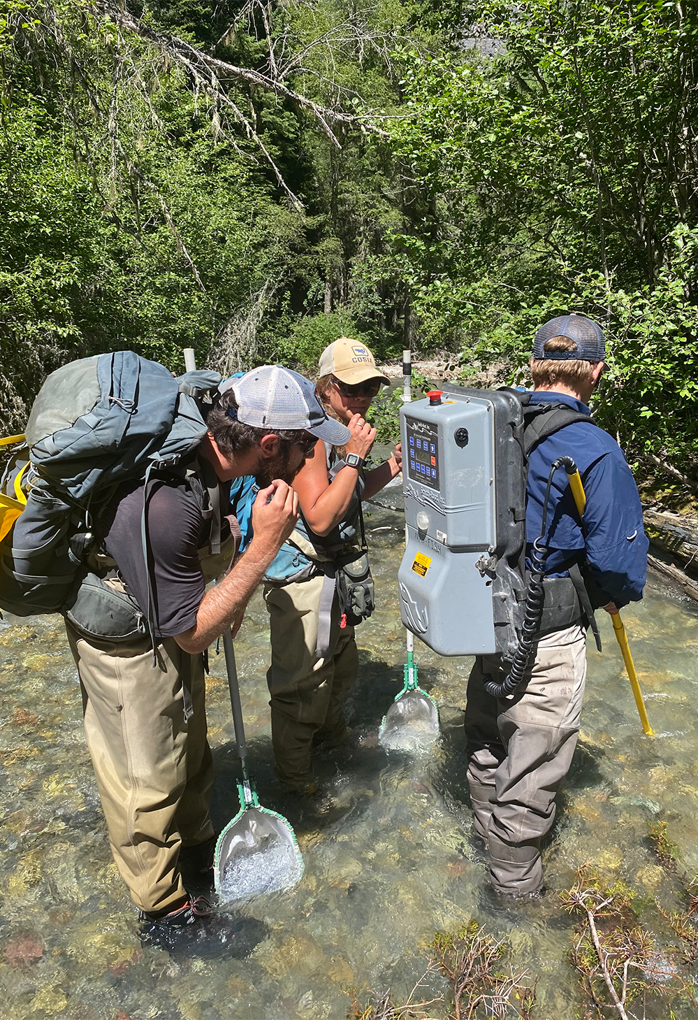 A team of scientists inspect a backpack on a crew member while wading in a river