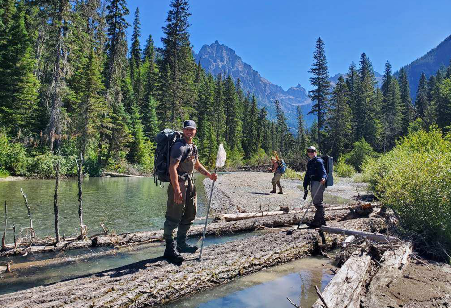 A team of scientists stand along the shore of a river in mountainous backcountry