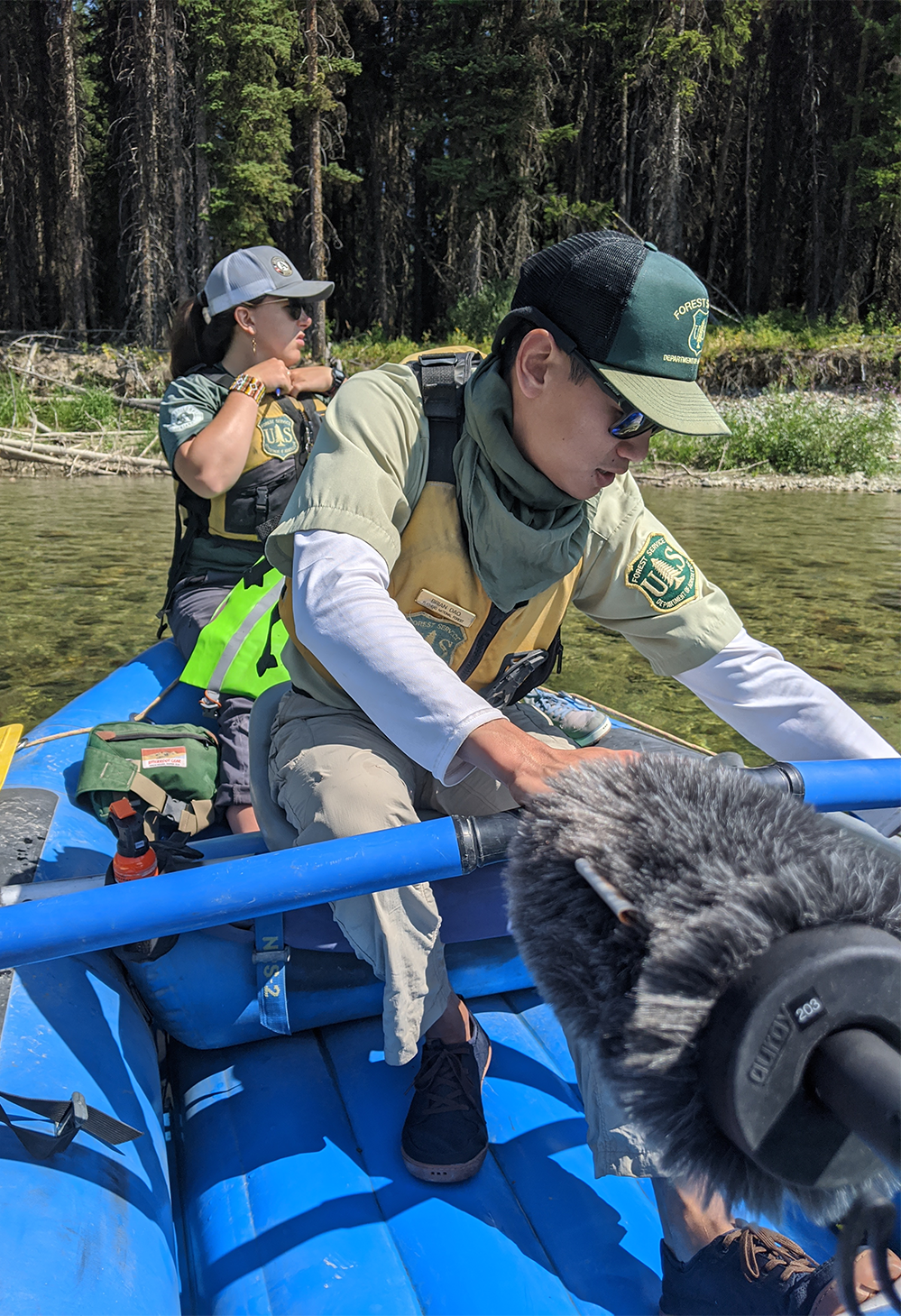 Two national forest river rangers float on a kayak while being recorded for a podcast