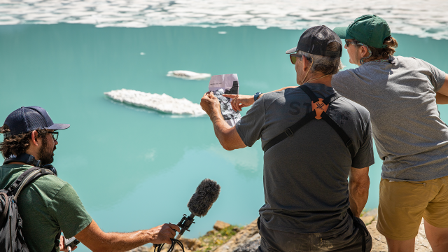 A park ranger holds a microphone and records a podcast while USGS scientist Lisa McKeon lines up a repeat photo in front of a turquoise lake in Glacier National Park