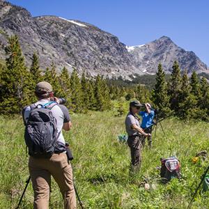 People looking through binoculars at mountains.