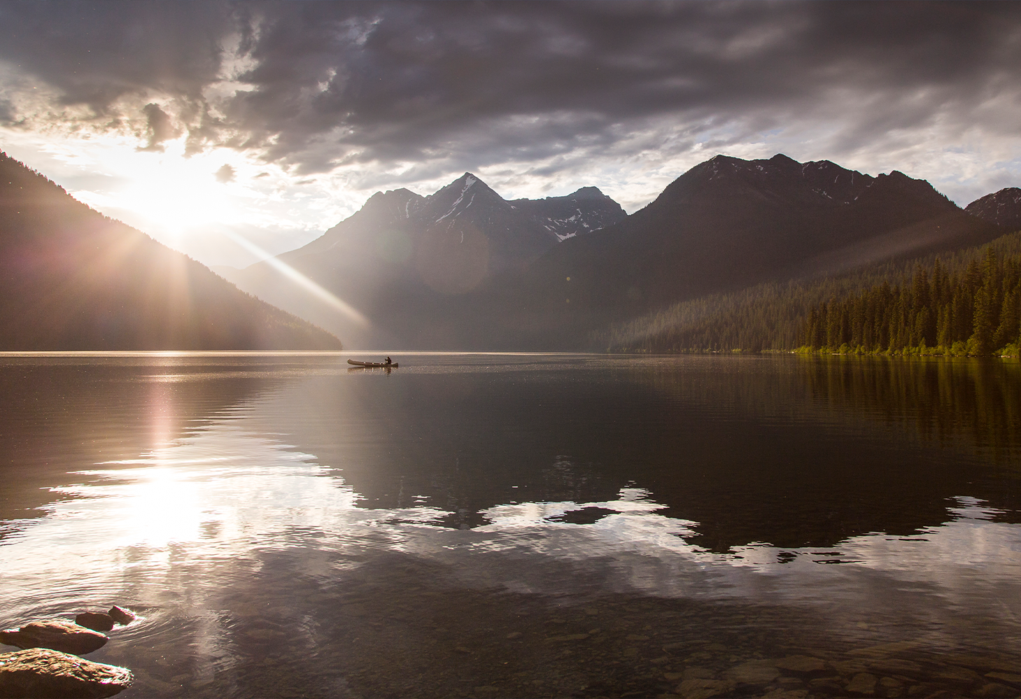 The sun sets behind a mountain range with an alpine lake in the foreground