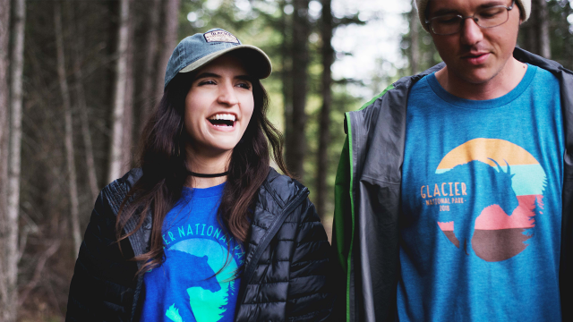 A woman and man wearing Glacier National Park tees smile and walk along a trail in a forest