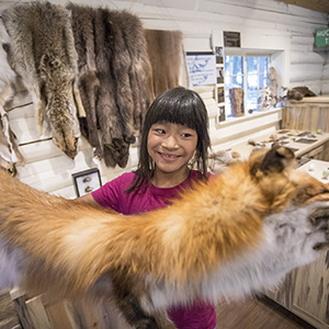 Kid in nature center holds up a fox pelt.