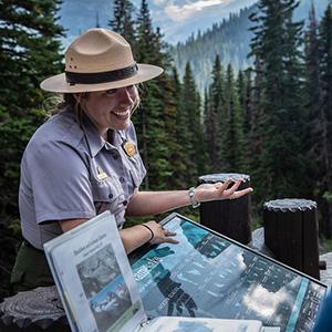 Ranger standing in front of interpretive sign explaining glaciation to park visitors.