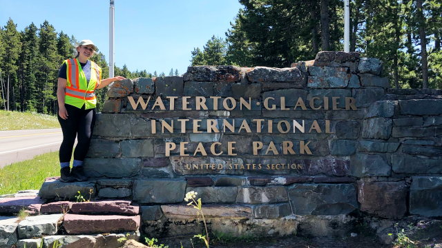 A woman stands next to a brick sign that says Waterton-Glacier International Peace Park United States Section