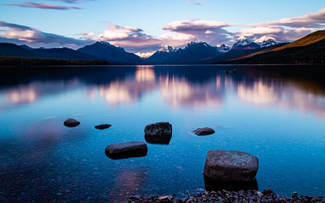 An alpine lake glows blue and purple and orange during sunrise with snowcapped mountains in the distance