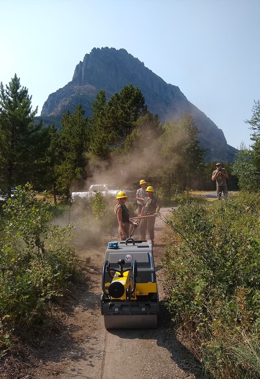 A group of trail crew workers stand near a drum roller machine to flatten a trail with a tall mountain in the background