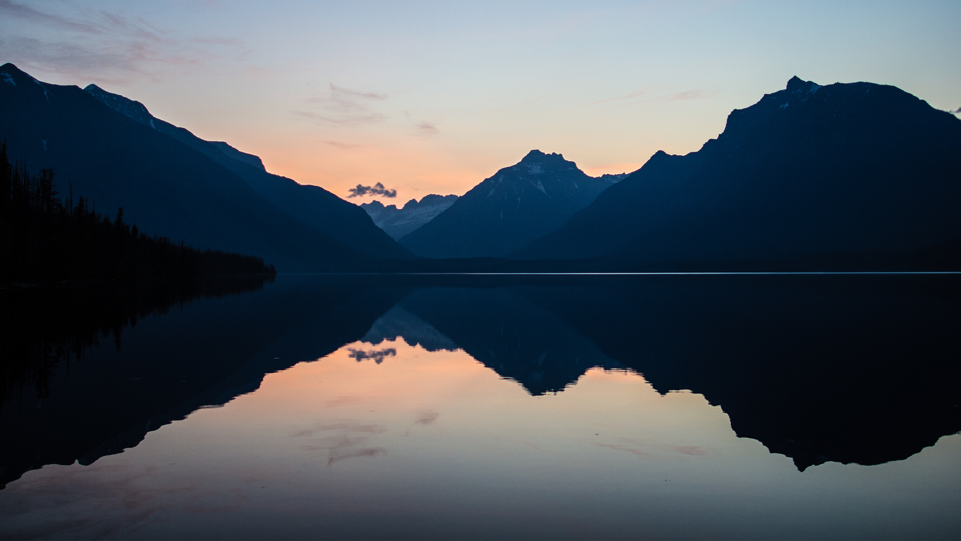 Sunrise on an alpine lake with silhouettes of mountains off in the distance