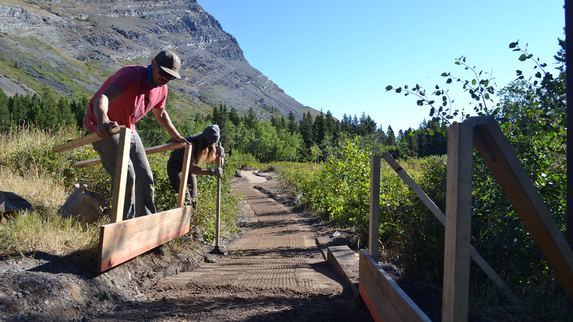 A team of trail crew workers install a bridge on a newly flattened trail with mountains in the background