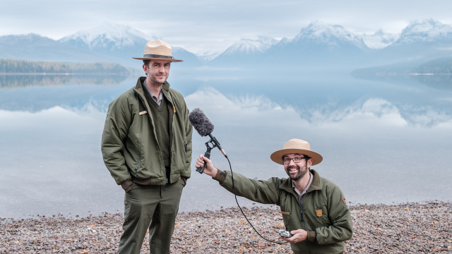 "Two park rangers pose in front of an alpine lake while holding a microphone to promote Glacier National Park's new podcast ""Headwaters"""