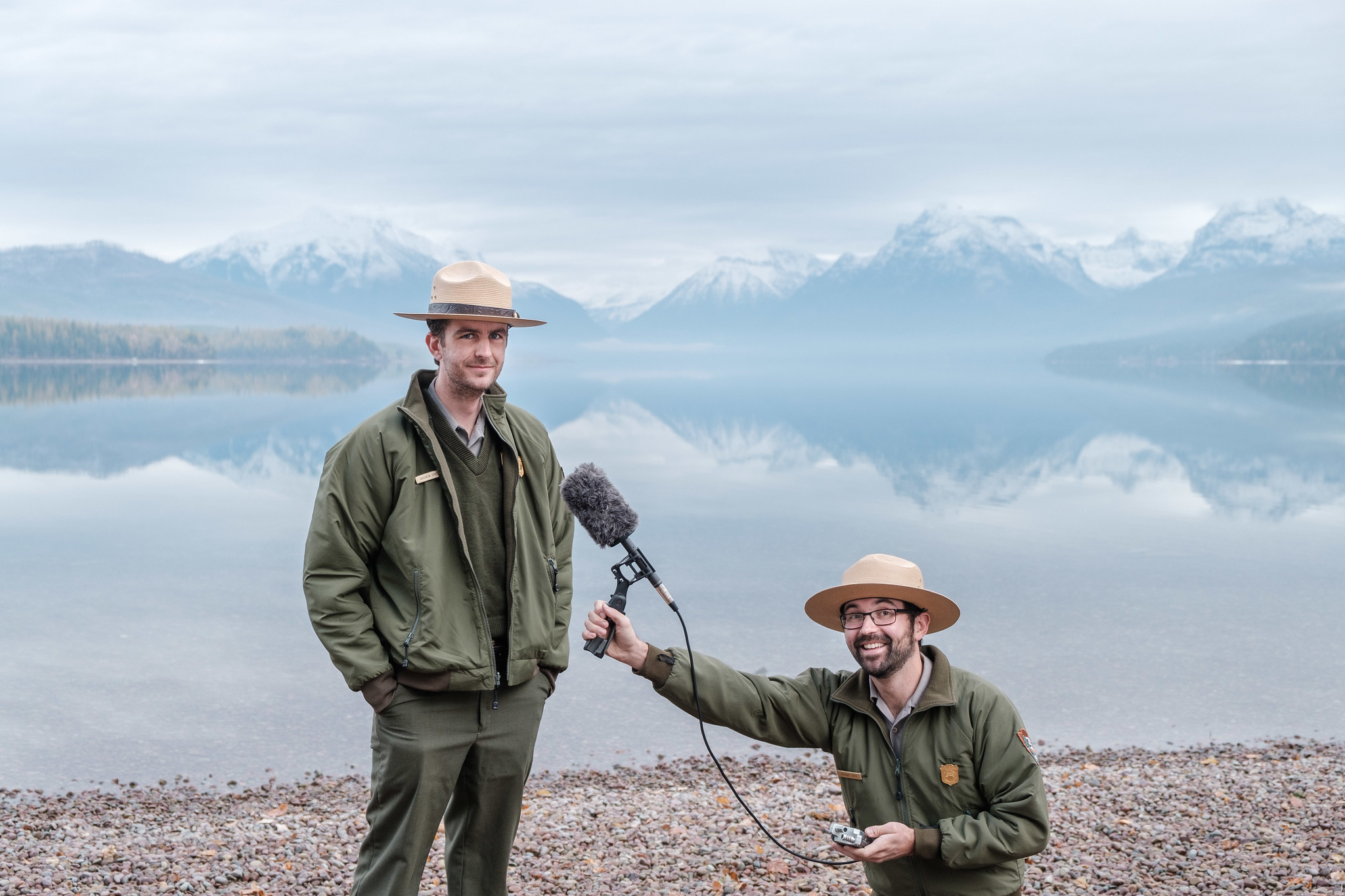 Headwaters Podcast Hosts Andrew Smith and Michael Faist posing with a shotgun mic in front of Lake McDonald.