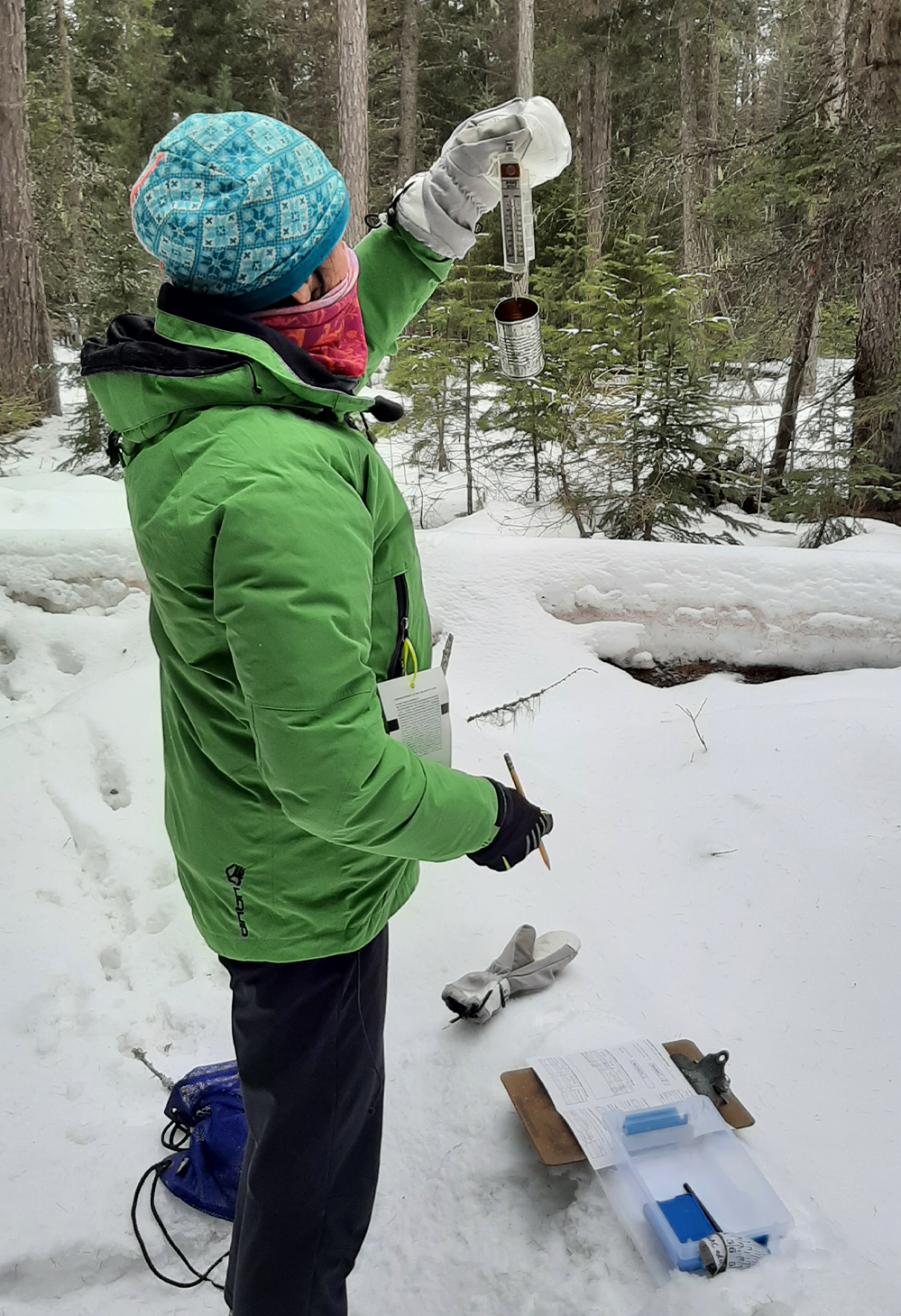 A teacher takes a snow sample outside during the winter session of the workshop Flathead Watershed Through The Seasons