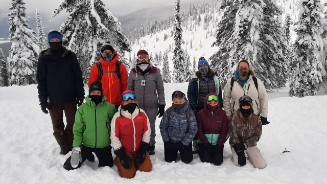 A group of teachers pose together in front of a snowy mountain landscape