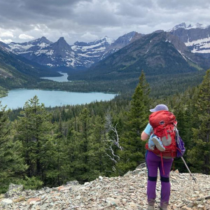 Hiker looking at forest, lake and mountains.