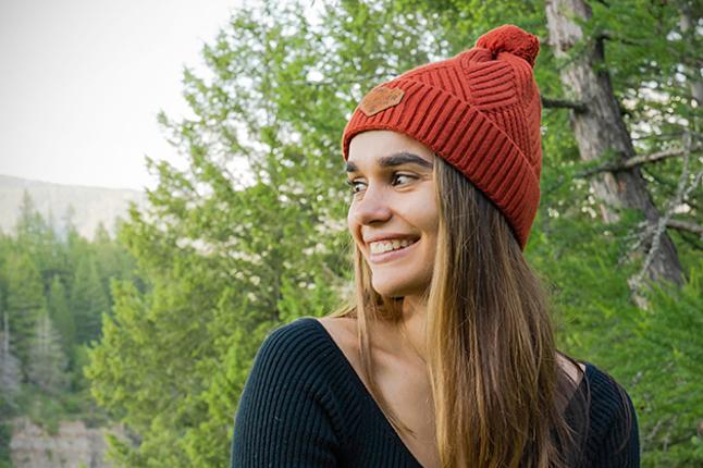 Una mujer con un gorro rojo con arboles en el fondo.