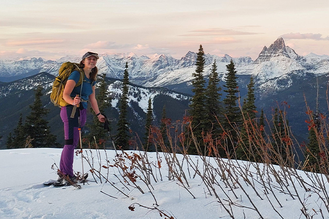 Woman snowshoeing with snowy mountains in background
