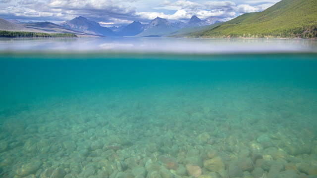 A split level image showing mountains above water, and colorful rocks under water
